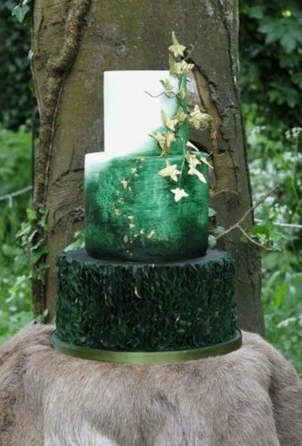 a jaw-dropping enchanted forest wedding cake with a dark green ruffle, an ombre green and white tiers, with gold edible leaves