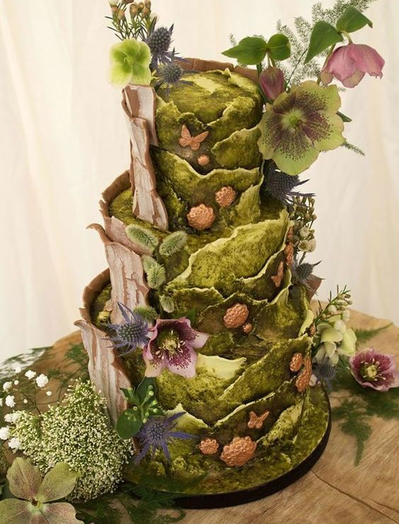 a jaw-dropping enchanted forest wedding cake with green moss-like buttercream tiers, thistles, butterflies, blooms and greenery just wows