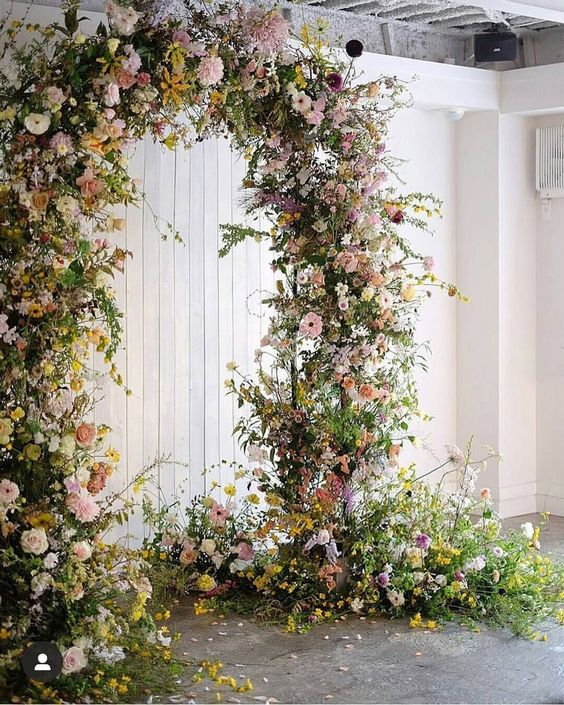a jaw-dropping garden wedding arch covered with greenery, yellow, blush and white blooms and some arrangements at the base looks fantastic
