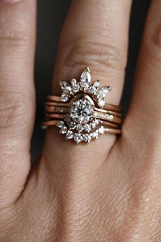 a jaw-dropping vintage stacked engagement ring with a central round one, two lower arched diamond rings and an upper large diamond arched one