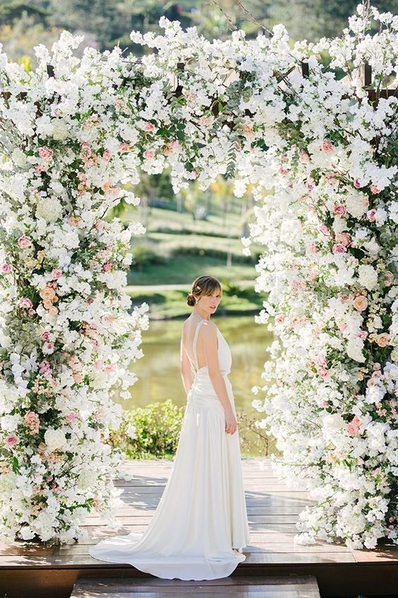 a jaw-dropping wedding arch covered with greenery, white and pink blooms and a view of the lake are fantastic for a garden wedding