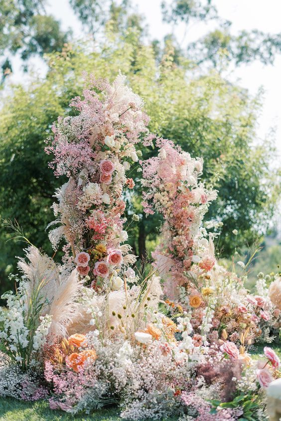a jaw-dropping wedding arch with pink, orange and white blooms, dyed baby's breath and pampas grass is gorgeous for a garden wedding