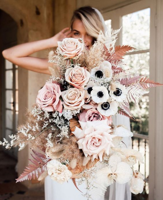 a jaw-dropping wedding bouquet of blush and peachy pink roses, white anemones, orchids, spray painted ferns and grasses