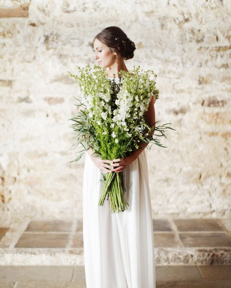 a large white bloom and greenery and grass long stem wedding bouquet is a fantastic solution for a spring or summer bride