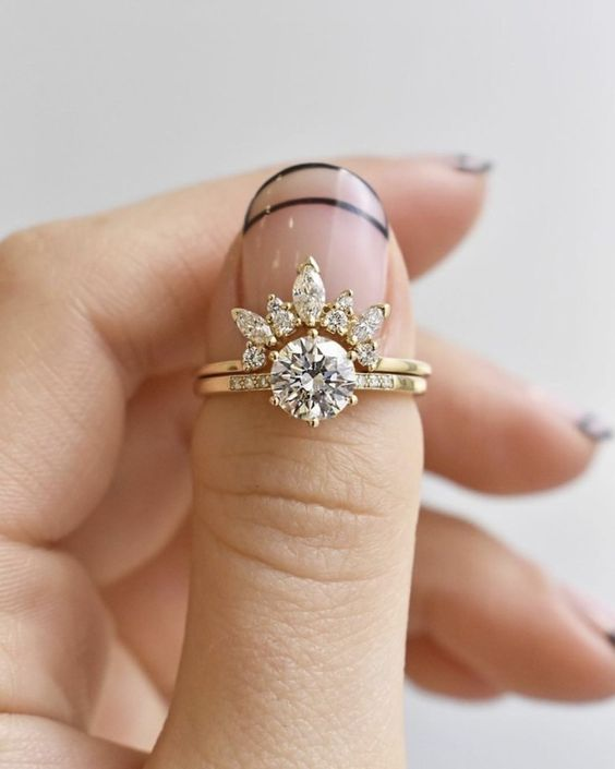a lemon gold stacked engagement ring with a large round solitaire and an arched diamond ring to accent it