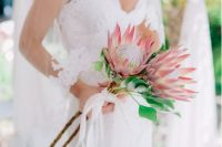 a long stem wedding bouquet of king proteas and white ribbons is a lovely idea for a tropical or summer bride