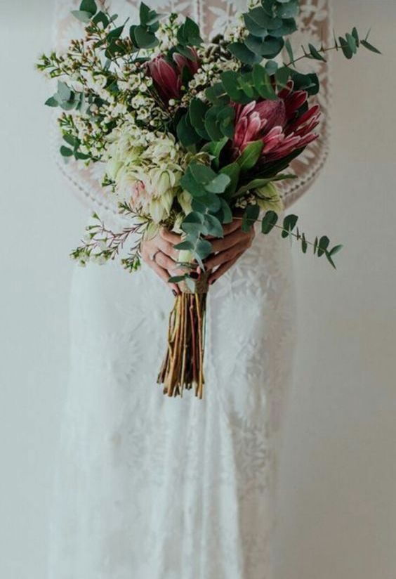 a long stem wedding bouquet of king proteas, eucalyptus, waxflowers is a beautiful idea with much texture and dimension