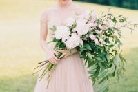 a long stem wedding bouquet with blush peonies and other blooms and greenery for a romantic and delicate spring bride