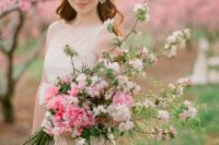a long stemmed wedding bouquet with hot pink peonies, pink cherry blossom and striped ribbons is amazing for a spring bride