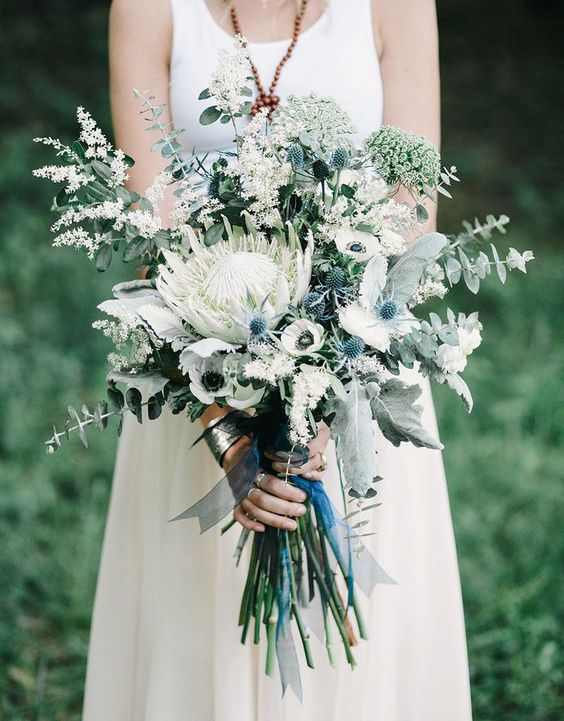 a lovely and chic long stem wedding bouquet with a white king protea and smaller white blooms, greenert and thistles plus blue ribbons
