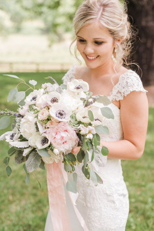 a lovely and delicate wedding bouquet of white and pink peonies, white anemones, eucalyptus and blush ribbons
