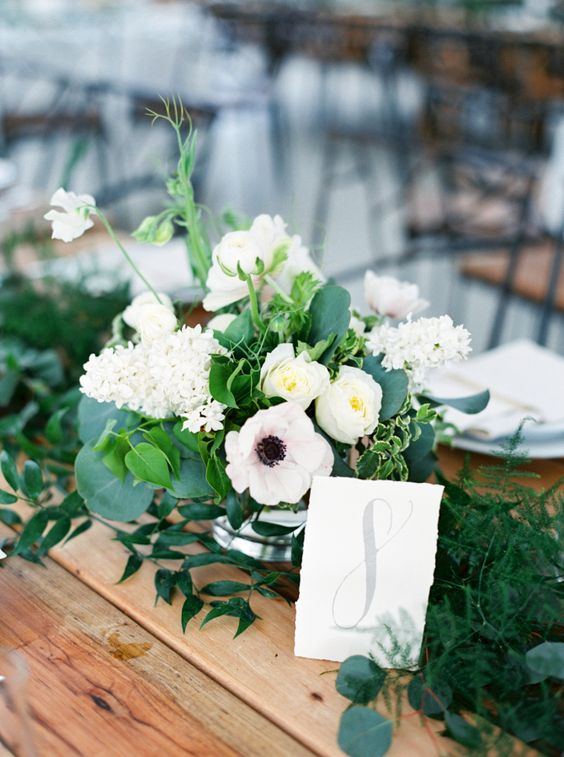 a lovely and fresh wedding centerpiece with white hydrangeas, anemones and ranunculus, greenery and an additional greenery table runner