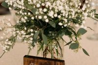a lovely and simple baby's breath wedding centerpiece with some fern and eucalyptus is a cool idea for a rustic tablescape