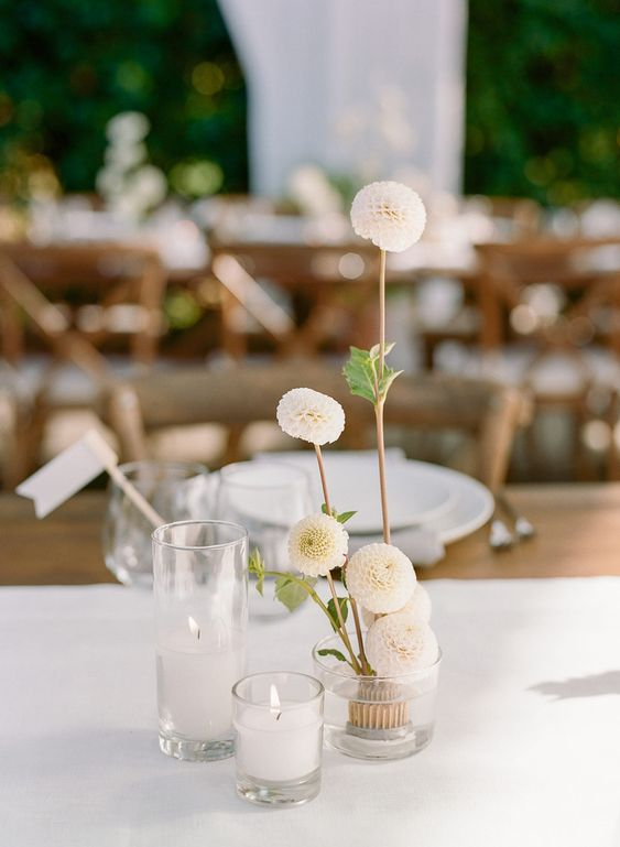 a lovely cluster wedding centerpiece of a couple of candles and white dahlias in a vase is a chic idea that you may realize yourself