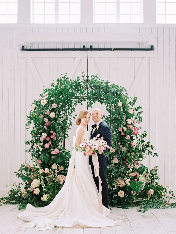a lovely garden wedding arch decorated with greenery, blush and pink blooms and arrangements at the base looks lush and beautiful