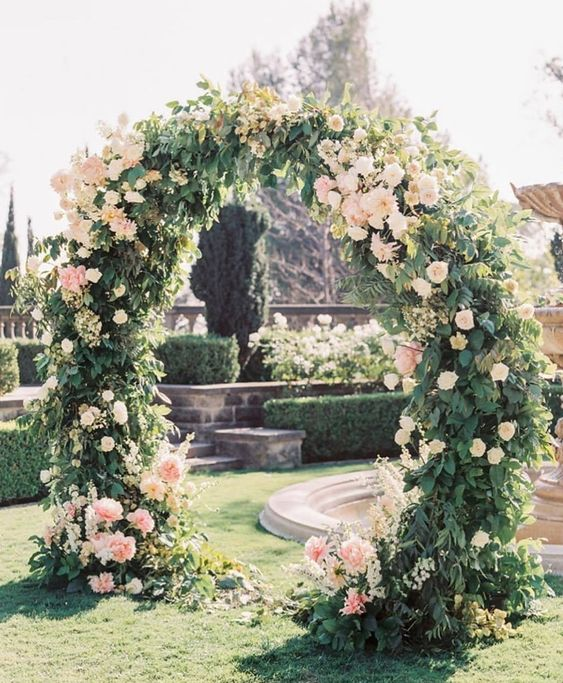 a lovely round wedding arch covered with greenery and with some blush flowers here and there is a very chic and elegant idea for a garden wedding