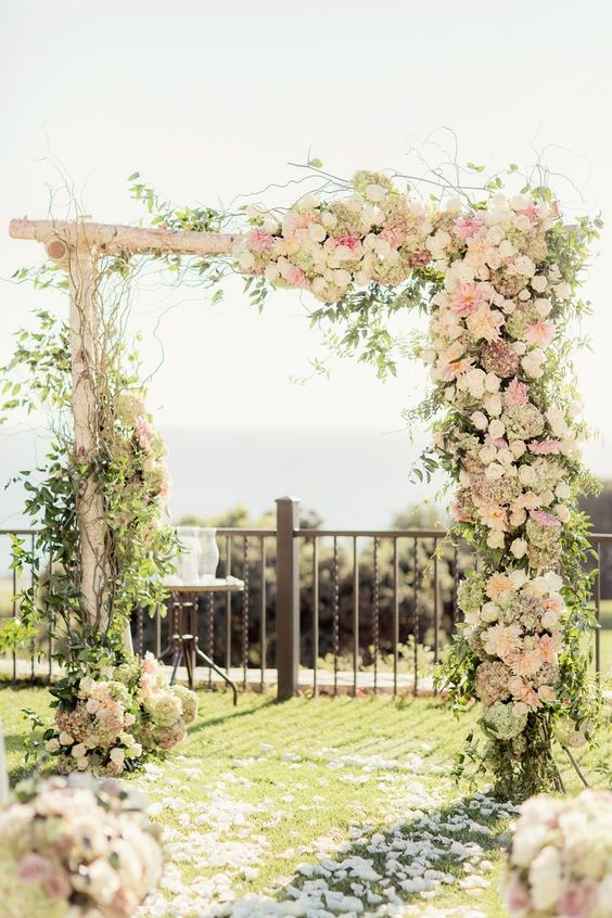 a lovely rustic wedding arch of branches, with greenery, twigs, blush and white rustic blooms is idea for spring or summer