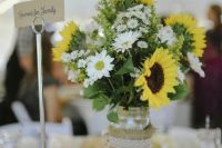 a lovely rustic wedding centerpiece of a jar wrapped in burlap, daisies, sunflowers and some foliage is a cool idea