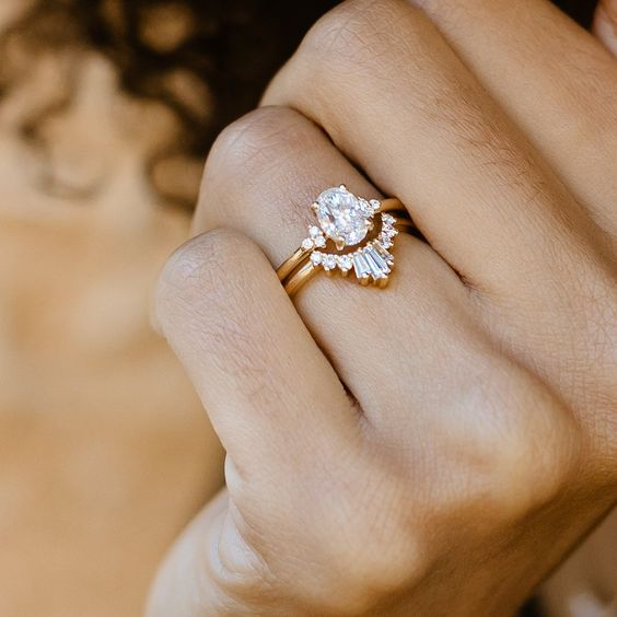 a lovely stacked engagement ring with a central oval diamond and an arched diamond upper ring isn't too much in your face