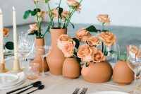 a lovely summer or fall wedding centerpiece of terracotta vases and rust-colored roses plus blush candles is chic