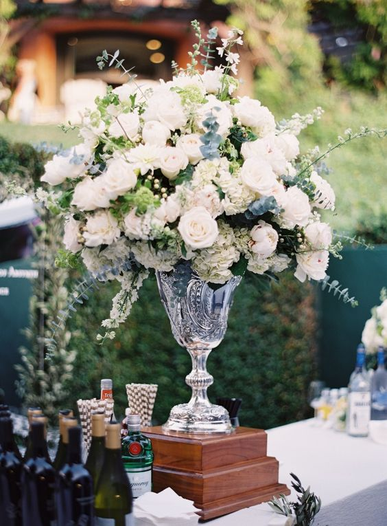 a lovely tall wedding centerpiece of a crystal vase, white blooms and lots of greenery and eucalyptus is a chic idea