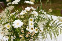 a lovely vintage-inspired wedding centerpiece of daisies, ferns and some wildflowers and seed pods is a very cool and romantic idea