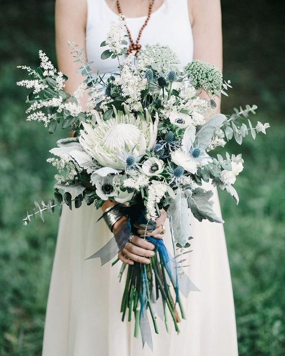 a lovely wedding bouquet of a king protea, white anemones and blooming branches, greenery and blue ribbons is chic for spring or summer