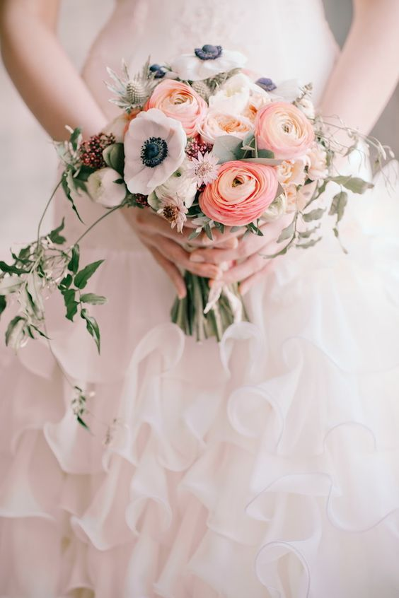 a lovely wedding bouquet of pink ranunculus, white anemones, blush peonies, greenery and thistles is amazing for spring and summer