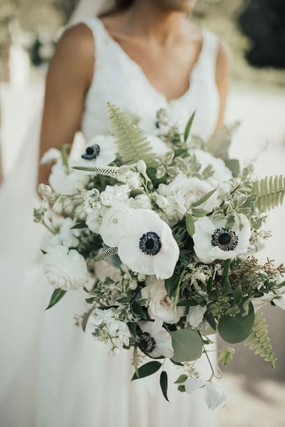a lovely wedding bouquet of white anemones and peonies, astilbe, greenery and fern leaves looks catchy and wild