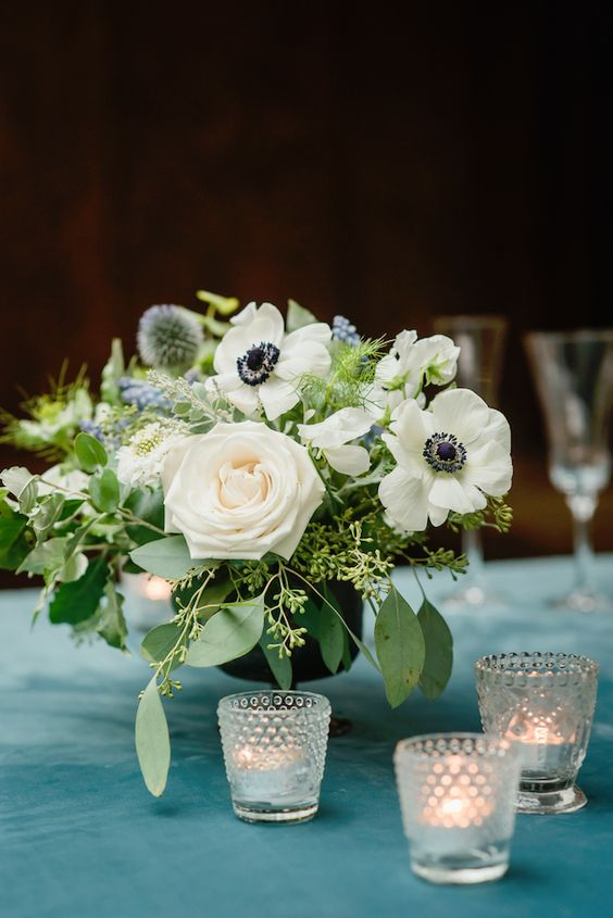 a lovely wedding centerpiece of white roses and anemones, greenery, blue blooms and allium plus eucalyptus and candle is a chic idea