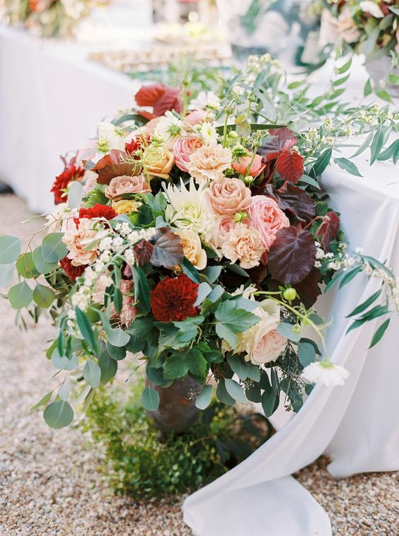a lush and bold fall wedding centerpiece of greenery, blush, deep red and peachy blooms and dark foliage is chic