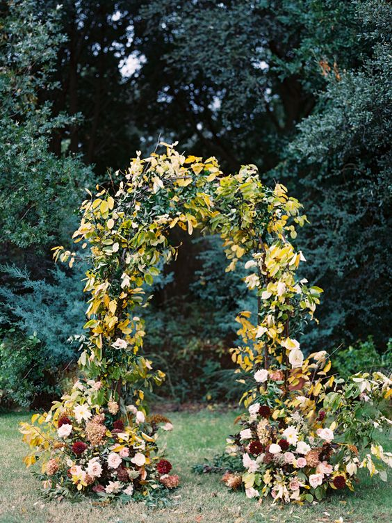 a lush fall garden wedding arch covered with greenery and fall leaves, with blush and burgundy flowers is a bright and cool idea
