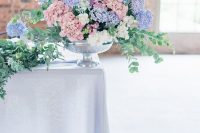 a lush pastel wedding centerpiece of dusty pink, white and lilac hydrangeas and eucalyptus is a gorgeous idea