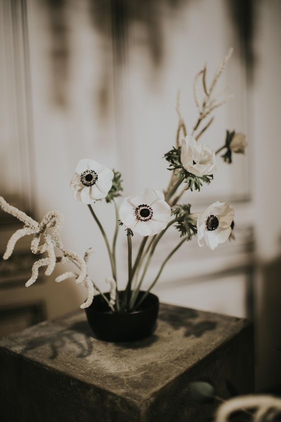 a minimalist wedding centerpiece of white anemones and astilbe in a black bowl is a lovely idea for a spring or summer wedding