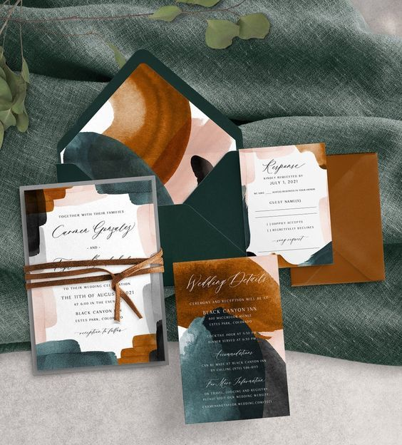 a moody abstract wedding invitation suite with teal, graphite grey, rust, blush touches, rust-colored envelopes and leather cord
