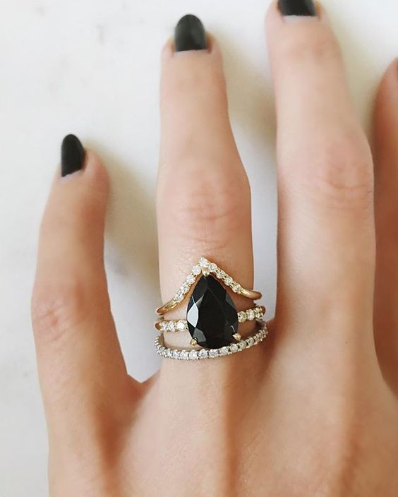 a moody stacked wedding ring with a triangle diamond upper one, a black opal central one, a usual diamond lower one