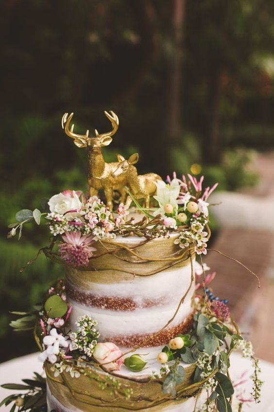 a naked wedding cake with gold touches, fresh blooms, greenery, twigs, berries and gold deer toppers is a perfect idea for an enchanted forest wedding