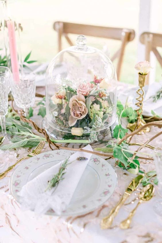a neutral and chic secret garden wedding centerpiece of blush and pink blooms and greenery in a cloche is a veyr playful idea