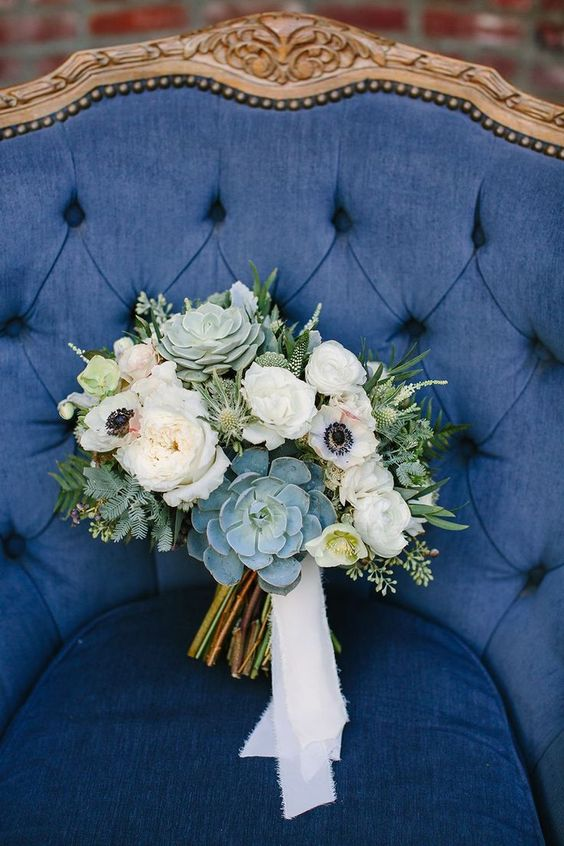 a neutral wedding bouquet of wihte anemones and peonies, succulents, thistles and greenery will match many bridal styles