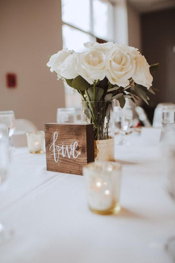 a pretty and simple wedding centerpiece of a gilded vase and white roses plus a wooden table number is a chic and easy solution