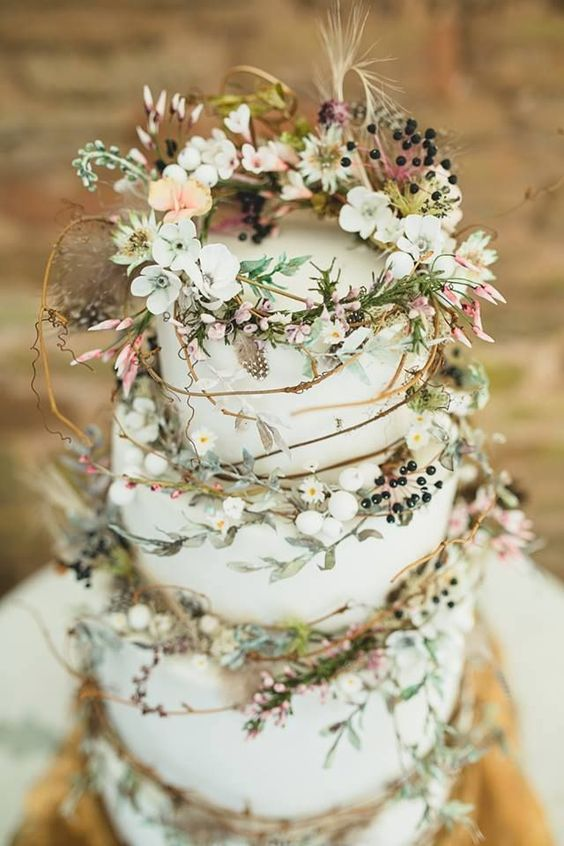 a pretty enchanted forest wedding cake with light green buttercream tiers, with twigs, blooms, berries and greenery plus some feathers is a great idea