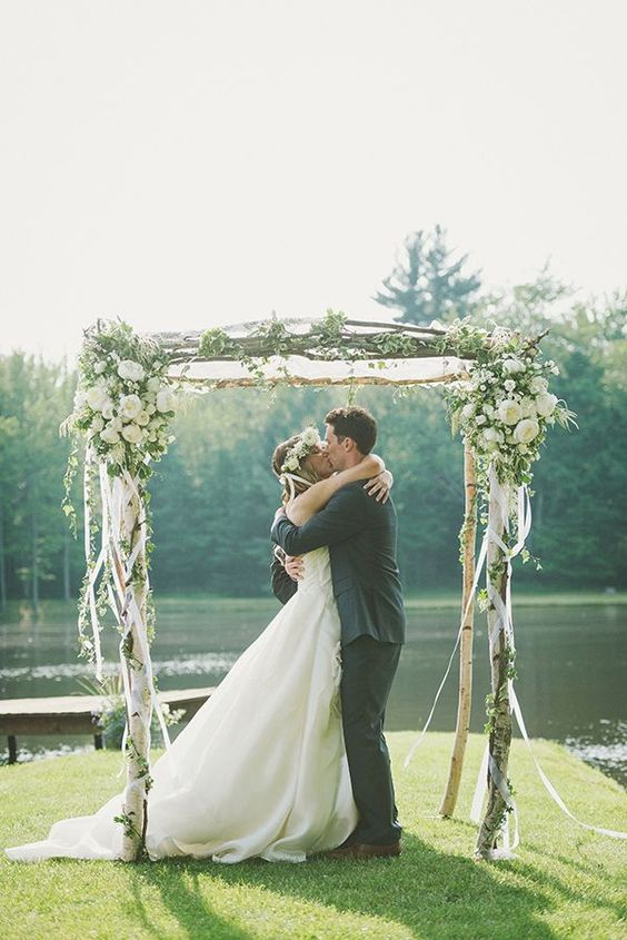 a pretty rustic wedding arch of brich branches, with white ribbons, white blooms and greenery and a cool backdrop of a pond