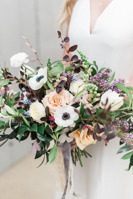 a pretty summer wedding bouquet of white anemones, peachy roses and blush peonies, greenery, lilac and dark foliage