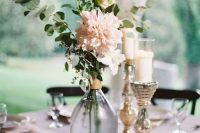 a pretty wedding centerpiece of pink dahlias, greenery, candles, a table number and mercury glass candleholders
