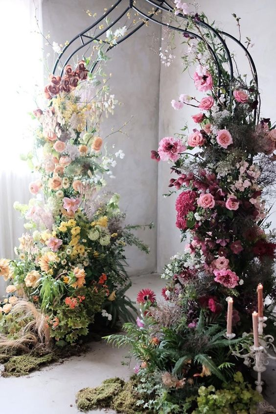 a refined and bright secret garden wedding arch of a quirky shape, with lush textural greenery, blush, yellow, orange, pink and purple blooms just wows