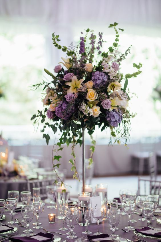a refined and lush secret garden tall wedding centerpiece of peachy, pink, blue and blush blooms and greenery in a gilded vase is wow