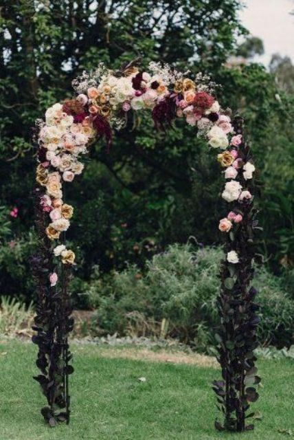 a refined fall garden wedding arch covered with leaves, with white, pink, burgundy and rust blooms is a lovely idea for a sophsticated wedding