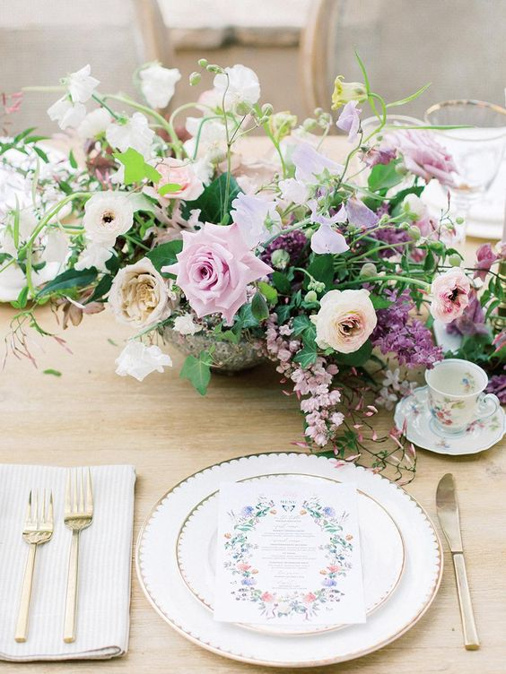 a refined garden wedding centerpiece of blush, lilac and white blooms, purple flowers and greenery amazes and wows