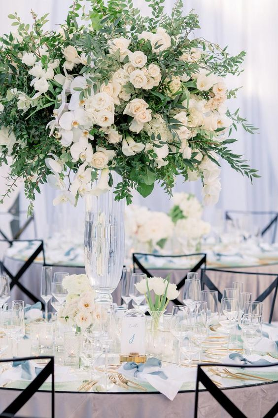 a refined garden wedding centerpiece of much greenery, white roses and orchids is a lush and very beautiful solution