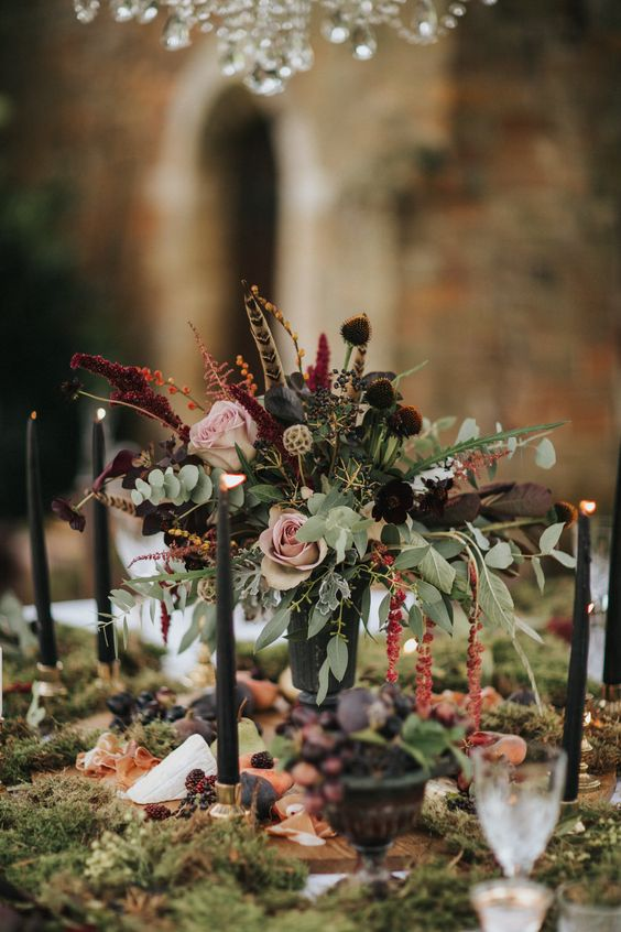 a refined moody secret garden wedding centerpiece of blush and dark blooms, greenery, berries and feathers is amazing for the fall